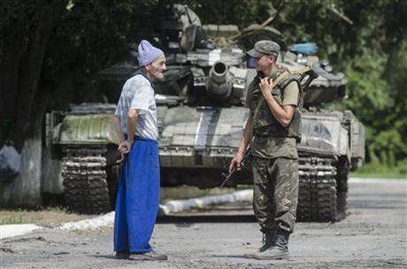A local citizen speaks to a Ukrainian government soldier guarding a checkpoint outside the city of Siversk, Donetsk region, eastern Ukraine, Saturday, July 12, 2014. Pro-Russian insurgents last week retreated from the strategic city of Slovyansk and holed up in Donetsk, a city of one million, and potentially the final frontier for the rebels.