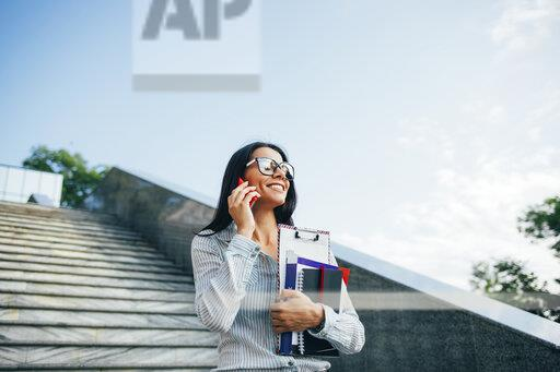 Smiling businesswoman using smartphone on stairs