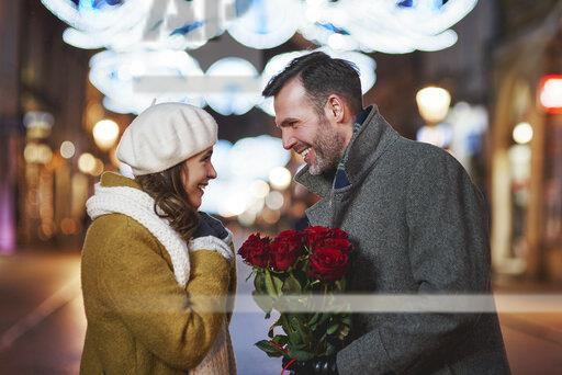 Man gifting his girlfriend bunch of red roses on Valentine's Day