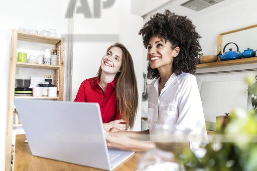 Two women working together in kitchen, using laptop