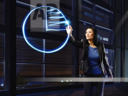 Asian businesswoman painting cake chart with light