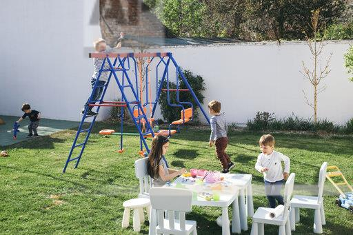 Kids playing in a garden, paining Easter eggs, climbing on swing
