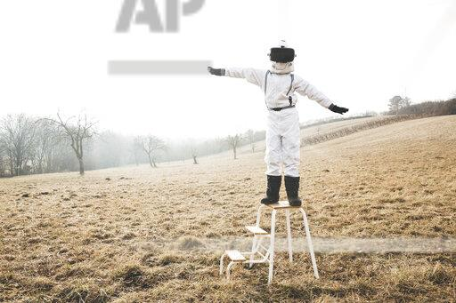 Boy wearing white space suit with raised arms on a step with virtual reality glasses