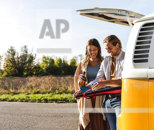 Couple on a road trip fixing surfboard at their camper