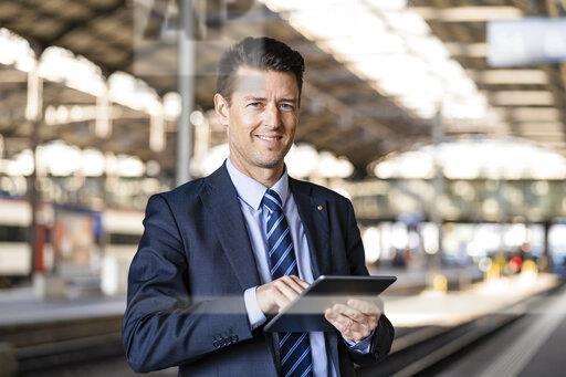 Portrait of smiling businessman using tablet at train station