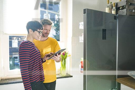Happy couple with tablet in front of their fridge doing online shopping for groceries