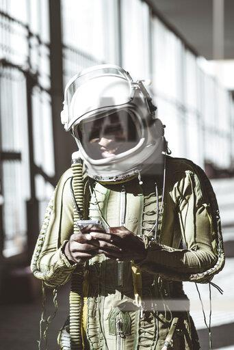 Smiling astronaut in spacesuit using smartphone
