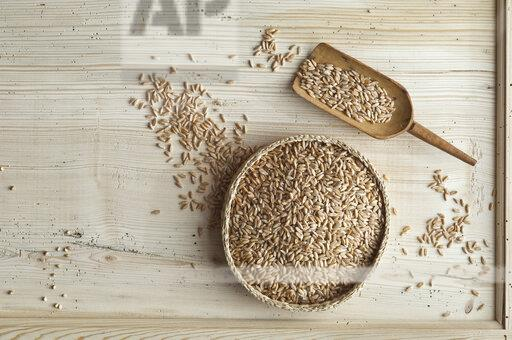 Organic spelt wheat in bast bowl, on wood, from above
