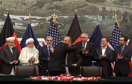 Afghanistan's national security adviser Mohmmad Hanif Atmar, center right, and U.S. Ambassador James Cunningham, center left, hug after signing the Bilateral Security Agreement at the presidential palace, in Kabul, Afghanistan, Tuesday, Sept. 30, 2014.