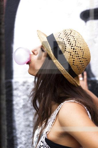 Profile of young woman blowing pink bubble gum