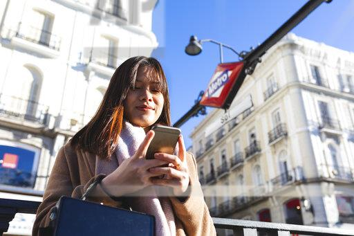 Spain, Madrid, smiling young woman at Puerta del Sol metro station checking her smartphone