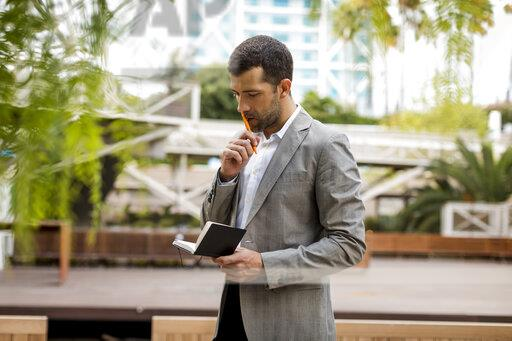 Businessman standing outdoors looking into notebook