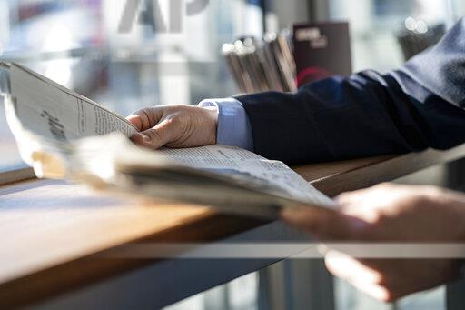 Close-up of businessman reading newspaper at the window in a cafe