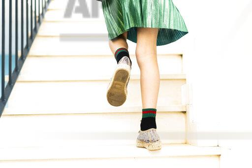 Girl wearing green skirt running upstairs