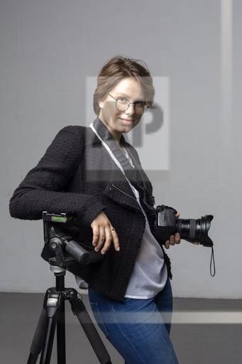 Portrait of smiling young photographer with camera and tripod