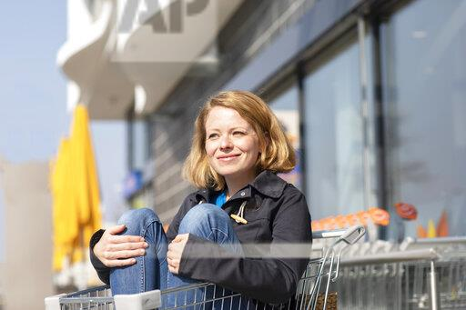 Portrait of smiling woman sitting in shopping cart in front of supermarket