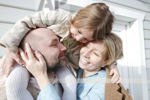 Happy family hugging in front of their house