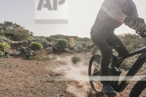 Spain, Lanzarote, partial view of mountainbiker on a trip in desertic landscape