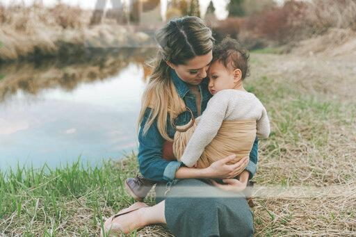 Mother holding her little daughter affectionately in nature