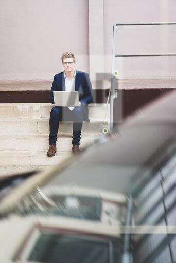 Young businessman with skateboard sitting outdoors on stairs using laptop