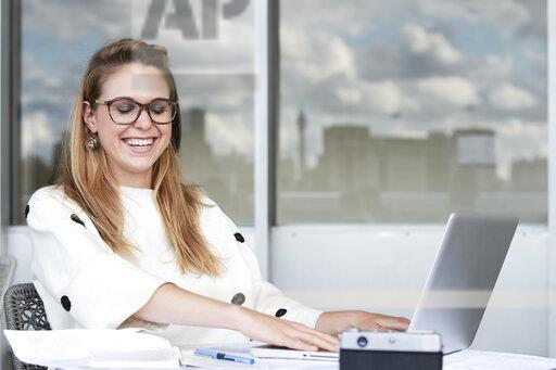 Portrait of laughing young businesswoman working on laptop in office