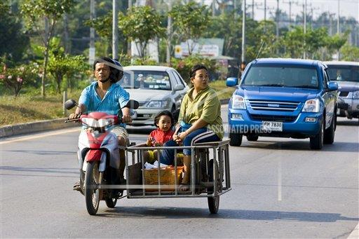 Creative Robert Harding Productions /AP Images A   Thailand 1161-2808 Family travel on a motorcycle and in a side trailer, Bangkok, Thailand
