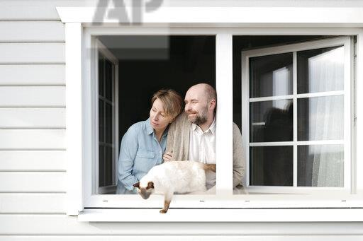 Couple with cat leaning out of window of their house