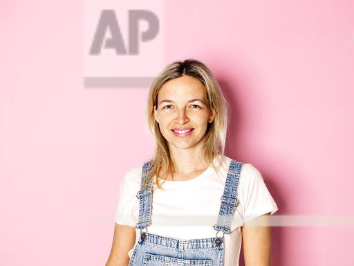 Portrait of smiling blond woman wearing dungarees in front of pink background
