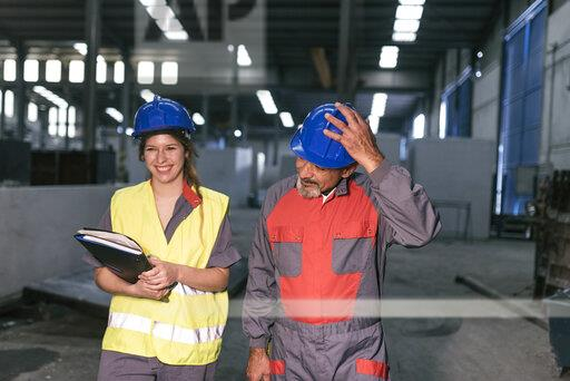Male and female worker wearing hard hats in factory