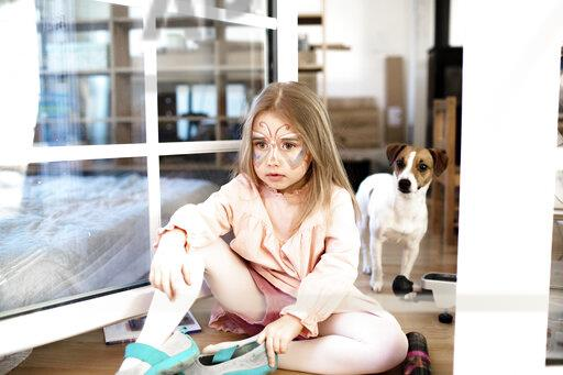 Blond girl made up as butterfly sitting on the ground, jack russel terrier in the background
