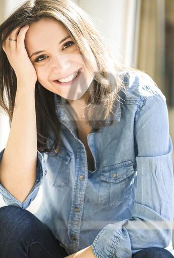 Portrait of happy woman wearing denim shirt at home