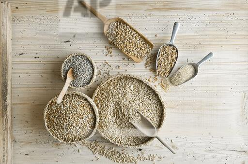 Organic wheat, rye shot, amaranth, spelt, buckwheat and oat on shovels and on wood, from above