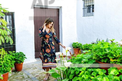 Spain, Cadiz, Vejer de la Frontera, fashionable woman looking at Callas at patio