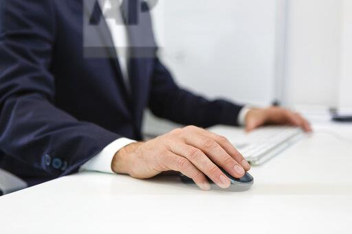 Close-up of businessman using computer at desk in office