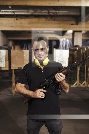 Portrait of man holding a rifle in an indoor shooting range
