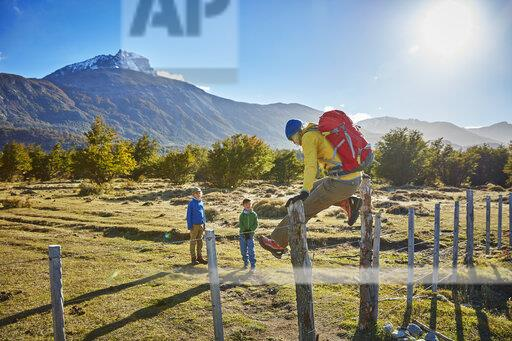 Chile, Cerro Castillo, mother with two sons on a hiking trip jumping over paddock fence