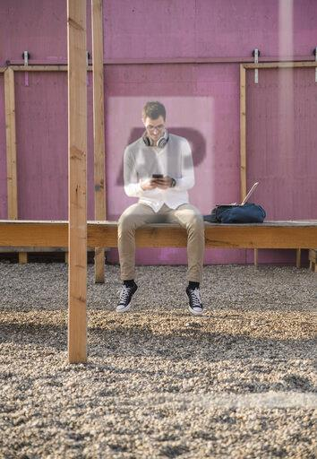 Young man sitting on platform using cell phone