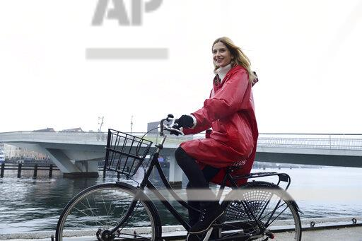 Denmark, Copenhagen, happy woman riding bicycle at the waterfront in rainy weather