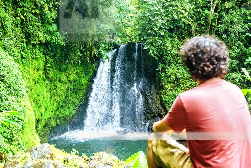 Costa Rica, sitting man looking at a waterfall