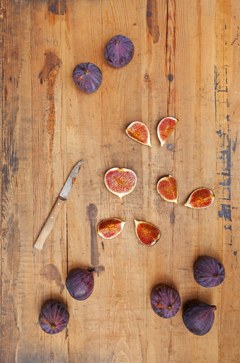 Kitchen knife and whole and sliced figs on wood