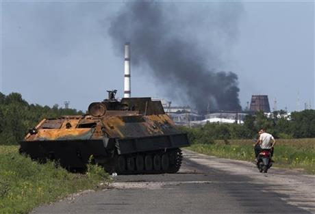 People ride a scooter past a destroyed pro-Russian fighters' APC near the city of Lisichansk, Luhansk region, eastern Ukraine Saturday, July 26, 2014. Volunteers from the Donbas Battalion, a volunteer militia for a united Ukraine, told The Associated Press their units, along with the Ukrainian army, regained control of Lisichansk on Friday. (AP Photo/Dmitry Lovetsky)