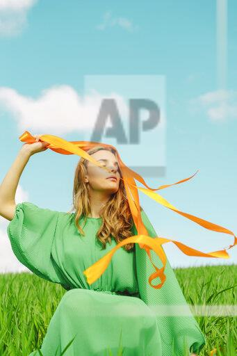 Young woman wearing a green dress sitting in a field with blowing ribbons
