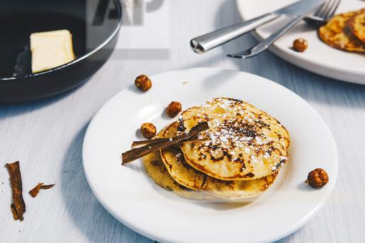 Pancakes on plate with hazelnuts, cinnamon sticks and icing sugar