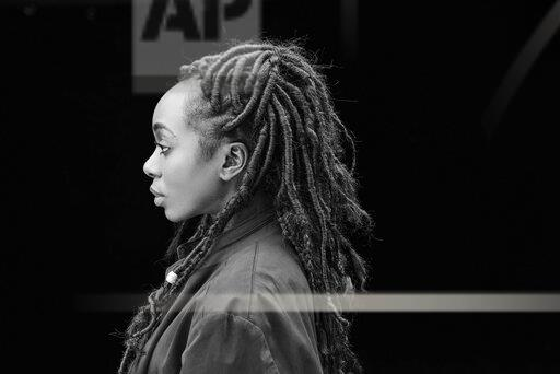 Profile of woman with dreadlocks in front of black background