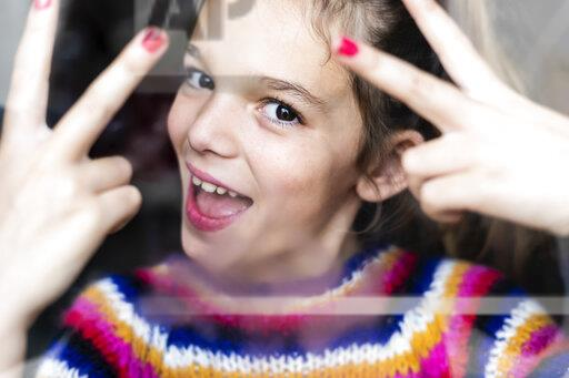 Portrait of happy playful girl in striped pullover behind windowpane