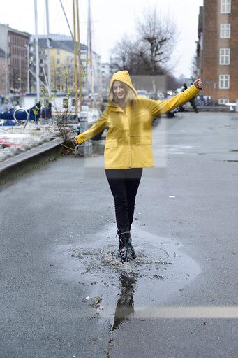Denmark, Copenhagen, happy woman jumping in puddles at city harbour