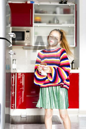 Girl in striped pullover in kitchen at home eating chocolate