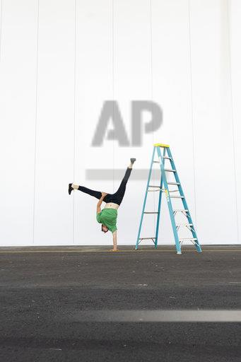 Acrobat training one-armed handstand next to ladder