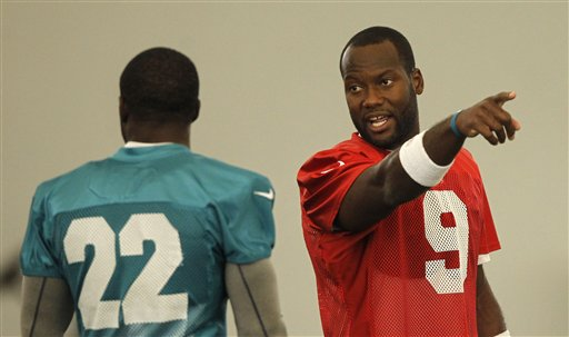David Garrard (9) talks to Reggie Bush