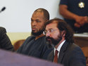 Siraj Ibn Wahhaj, left, sits next to public defense attorney Aleks Kostich at a first appearance in New Mexico state district court in Taos, N.M., Wednesday, Aug. 8, 2018, on accusations of child abuse and abducting his son from the boy's mother. Authorities were waiting to learn if human remains found at a disheveled living compound were those of Wahhaj's missing son. Authorities also allege Wahhaj was conducting weapons training with assault rifles at the compound near the Colorado border where they say they found 11 hungry children living in filthy conditions in a raid Friday. (AP Photo/Morgan Lee)